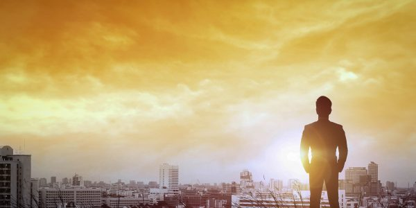 Silhouette of businessman to city way light the sunset.